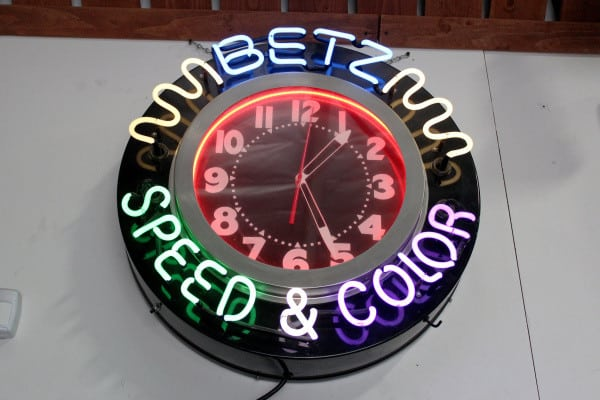 Stan Betz displays a neon clock from his business, Betz Speed and Color. He sold the paint shop to Sherwin Williams in 1993.